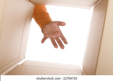 inside view of cardboard box with a hand trying to reach the content (selective focus)