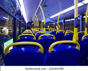 Inside view of London Double Decker bus at night. Rows of empty blue seats and nobody present.