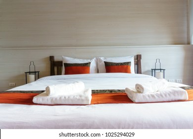 inside view of modern luxury double bed decoration for hotel, home, apartment, resort interior design with pillows, bath accessories and blanket.