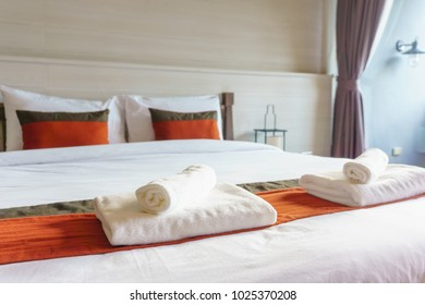 inside view of modern luxury double bed decoration for hotel,home,apartment,resort interior design with pillows, bath accessories and blanket.