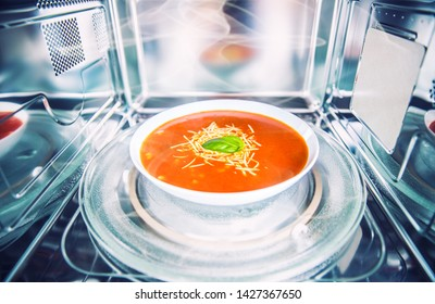 Inside view of new clean staniless microwave oven with a tomato soup in white plate.
