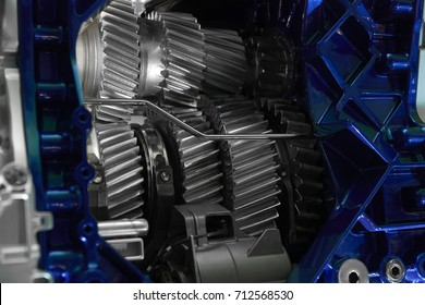 Inside view on gearbox cross section with gears and shafts. Automobile car truck gearbox with toothed wheels. Truck gearbox with open hood cover. Gears and shafts in housing