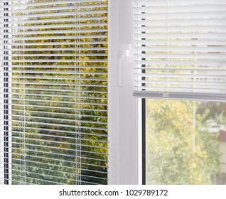 Inside view of part of the modern plastic window with white Venetian blinds, partly raised on one half of the window with mosquito net and blurred view of foliage across window