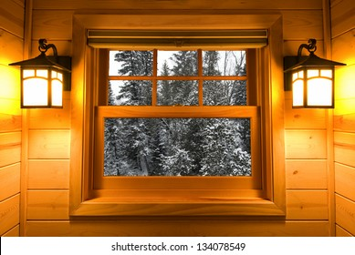 Inside view snow covered trees in a cedar cabin window with lights on