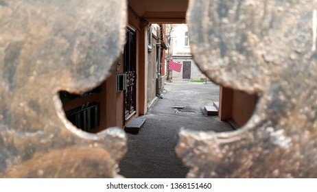 Inside view to traditional patio courtyard through blurred frames of cutout elements of old metal gates painted like aged bronze. Authentic courtyard of Odessa city in Ukraine. Grunge textures