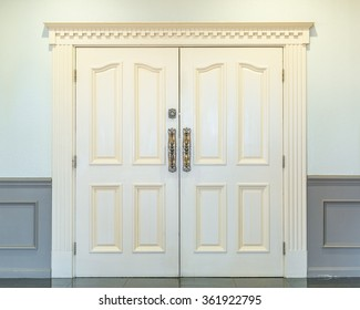 Inside white double doors with ornate handles and lock. Closed.