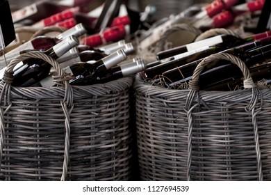 Inside a winery shop with red wine bottles in wicker baskets
