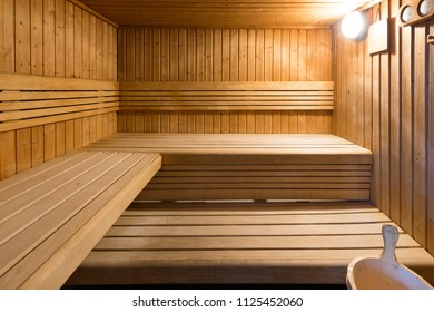 Inside wooden sauna, with benches and light on