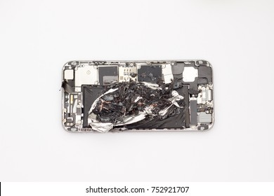 The inside workings of a mobile phone with back cover removed showing an exploded lithium battery