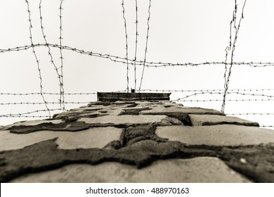Inside the yard of abandoned prison. Barbed wires and brick wall.