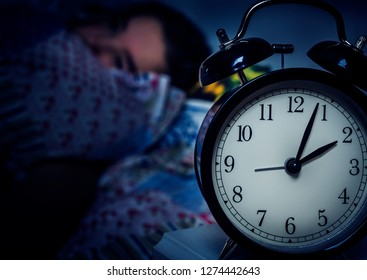 Insomnia. Alarm clock and teen girl in her bed