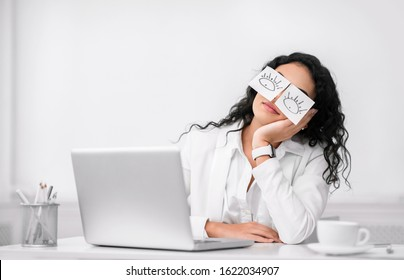 Insomnia. Lazy unproductive office worker girl wearing funny sticky notes on her eyes sleeping at workplace, copyspace