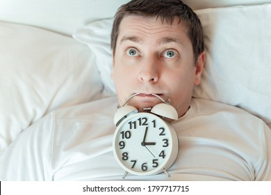 Insomnia. Man lies in bed with open eyes and alarm clock in mouth trying to fall asleep at night. Counting sheep awake. Stress thoughts in bedroom with white linen. Sleep disorder.