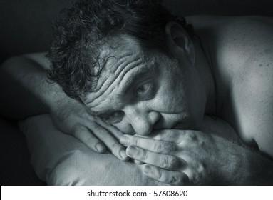 Insomnia. A man tries to fall asleep. Blue tinted