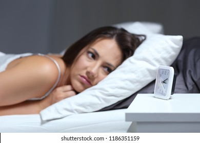 Insomniac woman bored looking at alarm clock in the bed in the night
