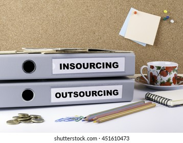 Insourcing and Outsourcing - two folders on white office desk
