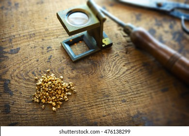 Inspecting gold. Gold nuggets with an vintage magnifying glass, with tools in background. intentionally shot with extremely shallow depth of field.