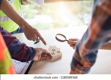 Inspection building concept, Inspector or engineer checking house construction by use magnifying glass on home model