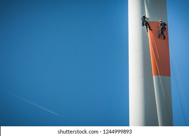 Inspection engineers abseiling from the rotor blade of a wind turbine in a North German wind farm on a clear day with blue sky.