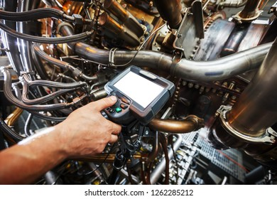 Inspection of a gas turbine engine using a Video Endoscope. Search for defects inside the turbine and shooting on video, photos using a measuring instrument. Copy-Space Video Endoscope. Gas turbine.