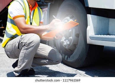 Inspection safety a trucks, truck driver holding clipboard with checking tire truck.