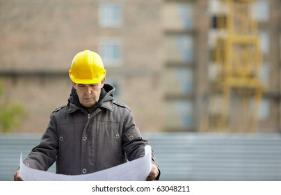 Inspector with blueprints on construction site, natural light, focus on foreground