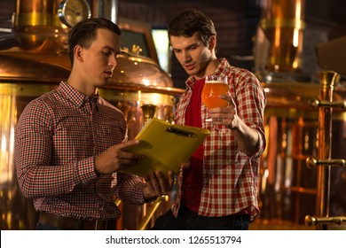 Inspector of brewery showing yellow folder to brewer. Worker of beer factory holding beer glassand looking down. Men in checked shirts working with production of alcohol beverage.