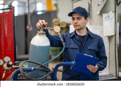 Inspector checking a gas tank in an industrial factory