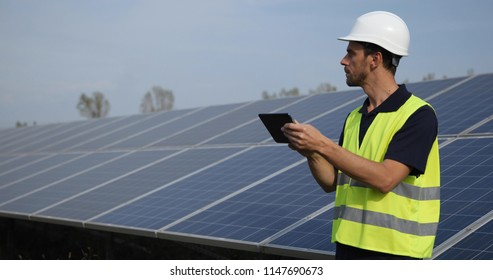 Inspector Engineer Man Holding Digital Tablet Working in Solar Panels Power Farm, Photovoltaic Cell Park, Green Energy Concept