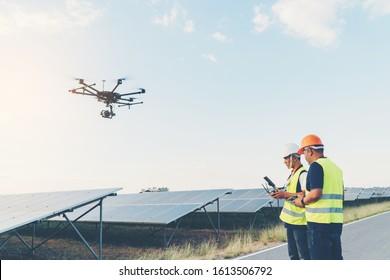 Ingenieurkonzept der Inspektoren; Techniker inspizieren und prüfen das Solarpaneel von Drone im Solarkraftwerk