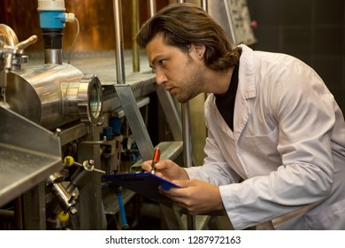 Inspector examining industrial equipment on beer factory. Serious man holding folder and writing with pen. Worker of brewery looking at machinery and controlling quality.