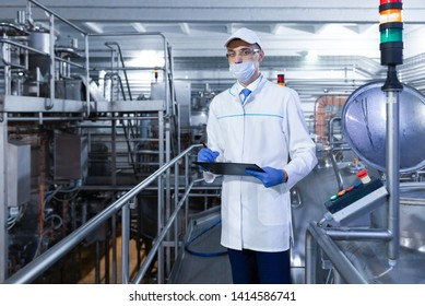 Inspector in a mask and a scrub stands with a folder-tablet in his hands at the dairy plant