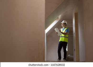 Inspector On Building Site With Clipboard