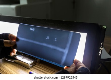 The inspector reviews radyography films of welds of the oil storage tank with light box at the office. ASTM 1A and 6 is an ASME standard penetrameter.