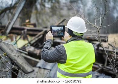 Inspector with tablet near collapsed building