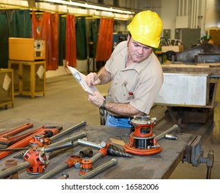 Inspector verifying the condition of available tools in a metal work shop.  Authentic and accurate content in accordance with industry code and safety standards.