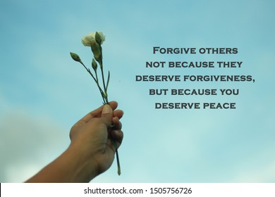 Inspiraitonal motivational quote-Forgive others not because they deserve forgiveness, but because you deserve peace. With young plant in hand on blue sky background.