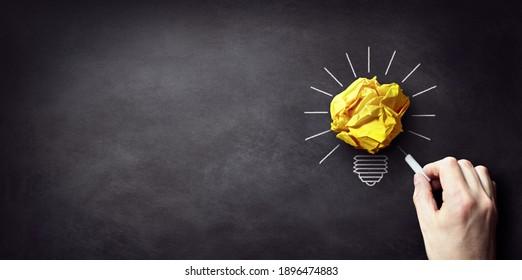Inspiration concept crumpled paper light bulb metaphor for good idea background on blackboard