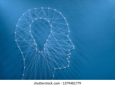Inspiration concept. Network of pins and threads in the shape of a cut out light bulb inside a human head symbolising creative thinking.