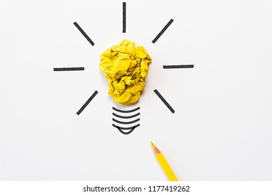 Inspiration and great idea concept. light bulb with crumpled colorful paper and yellow pencil on white background.