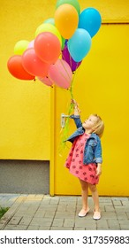 inspiration, happy little girl outdoors with balloons on a yellow background