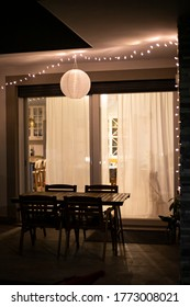 Inspiration home decor idea, with string lights and a globe solar lantern hanging on the ceiling in the front porch, over outdoor furniture, warming the backyard or garden in summer nights. Vertical.