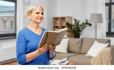 inspiration, memoirs and old people concept - portrait of smiling senior woman in blue sweater with diary or notebook and pencil over home living room background