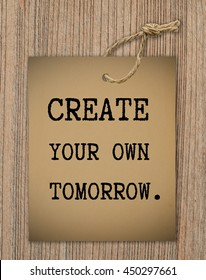 Inspiration quote, CREATE YOUR OWN TOMORROW on old paper tag on wooden texture background.