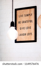"Inspiration quote frame hanging on the white bricks wall. ""Live simply Be grateful Give love Laugh Lots"""