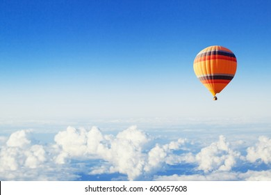 inspiration or travel background, fly above the clouds, colorful hot air balloon in blue sky