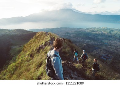 Inspiration and trekking concept. Group of hikers climbing a mountain at vacation. Hiker man standing at the top of the volcano looking the panorama.
