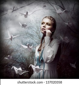 Inspiration. Woman with Flying White Origami Swans in Dark Mystic Forest