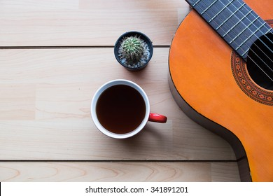 Inspirational background with classical guitar on a wooden table.cup of coffee for the music composer,vintage effect.
