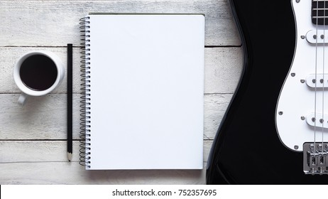 Inspirational background with an electric guitar on a wooden table while composing. Score sheet, a pencil and a cup of coffee for the music composer, Top view and a copy space for editor's text.